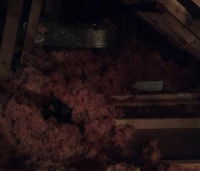 an attic space with wood planks and pink insulation